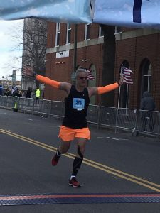 Image of Mike Nall crossing the finish line at the One City Marathon
